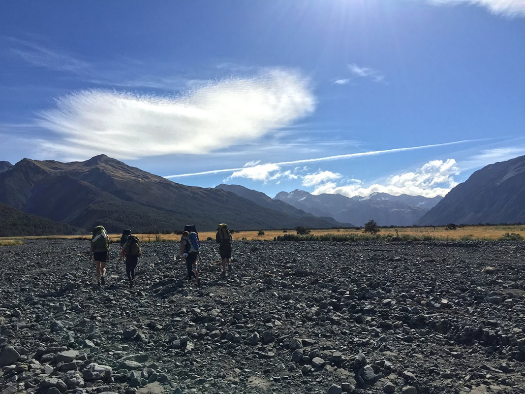 A group of backpackers walking towards an epic view of the mountains.