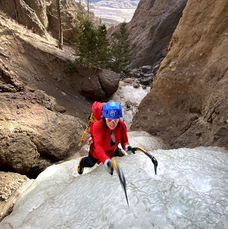 Natalie ice climbing with Grivel poles visible on her pack.