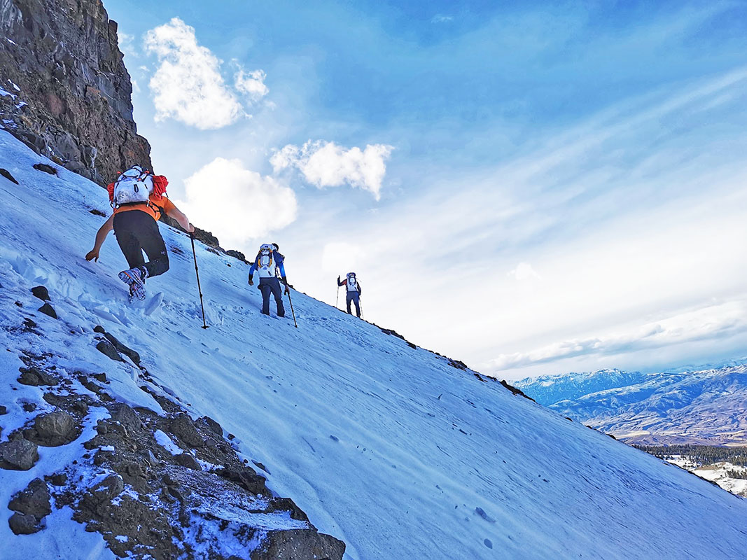 Mountaineer people in a line. All are using poles for stability on the slope.