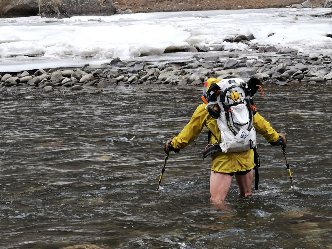 Aaron Mulkey is wearing no pants while up to his thighs in cold water. He uses the Grivel poles to keep his footing as he crosses.
