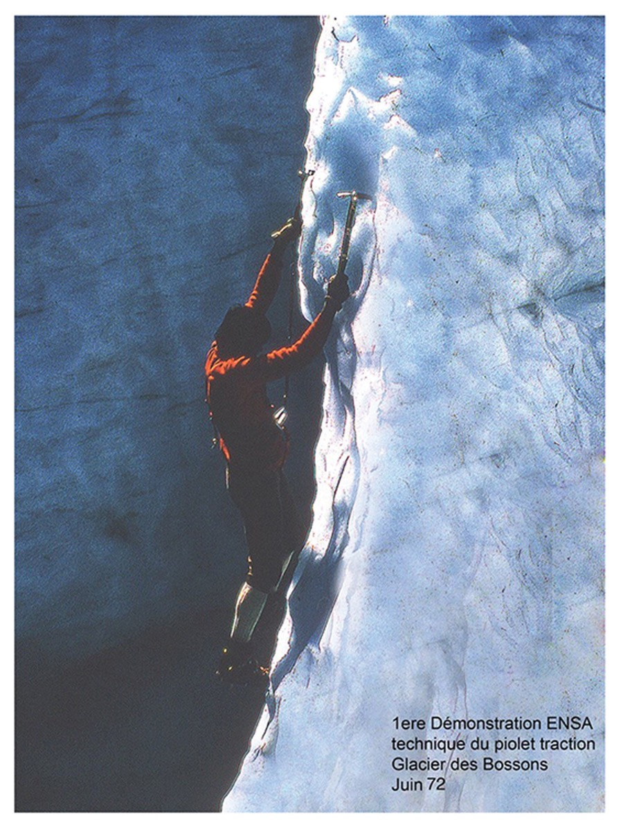 1972 photo of a man climbing with two ice climbing tools, ice climbing axes and crampons