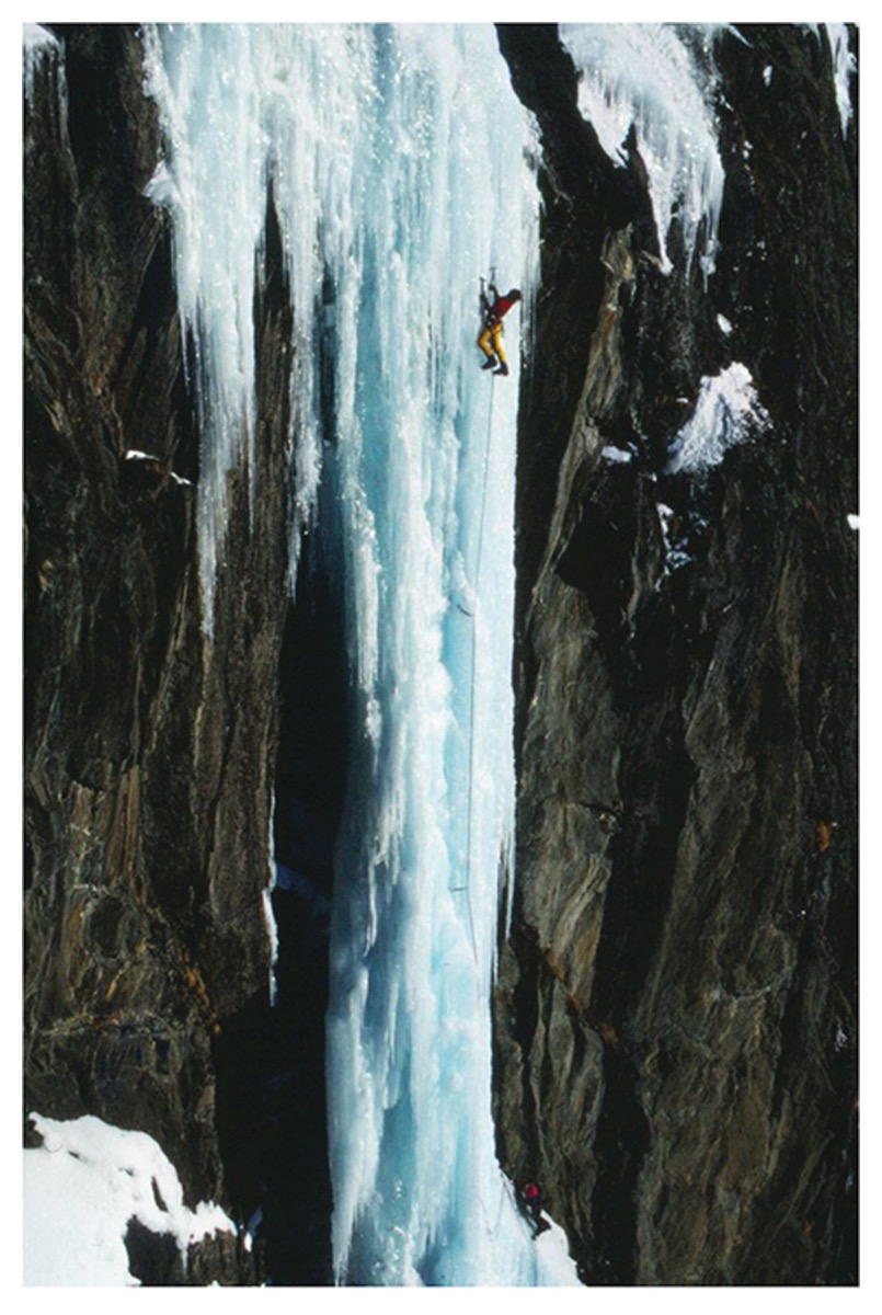 A man climbing a nearly vertical stretch of ice
