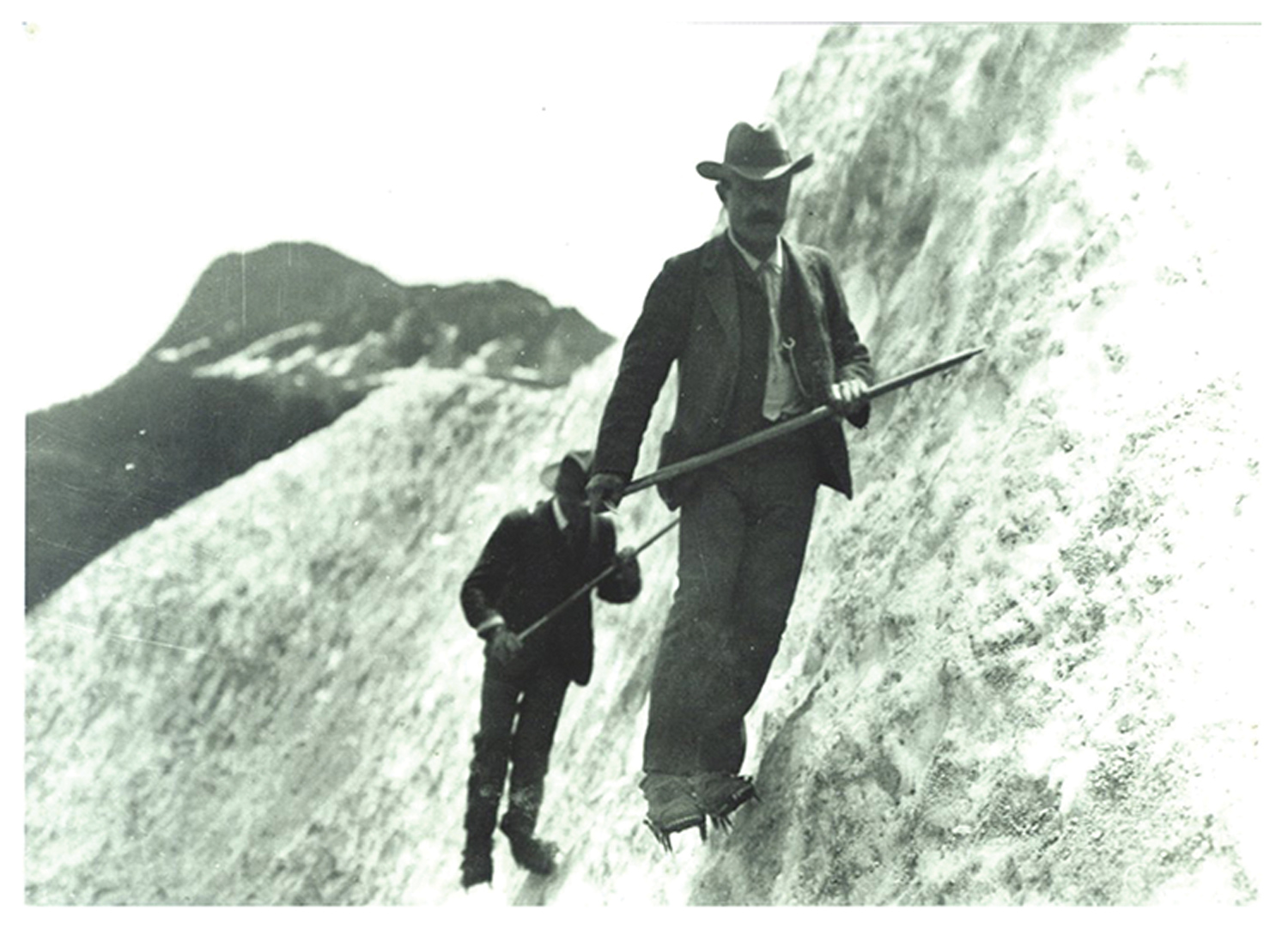Picture of some of the first ice climbing crampons, two men standing on an ice wall using crampons holding ice axes